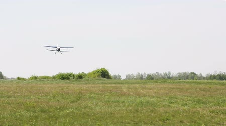 фюзеляж : Light single-engine aircraft lands on the field airfield. The aircraft sits on the green grass. Bottom view