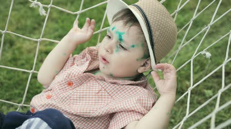 pus : Portrait of a small funny boy 2-3 years old with chicken pox in a hammock. Face and body of the child in green dots