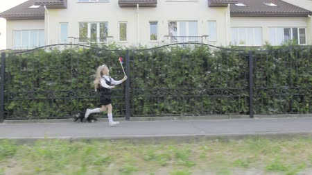 lapát : Little funny schoolgirl in school uniform and briefcase on his shoulders walking around the area. In the hands of the girl rainbow spinner. Steadicam shot Stock mozgókép
