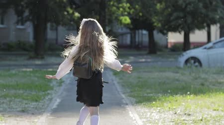 плевать : Portrait of a blonde schoolgirl 1-2 class with a portfolio. Girl in school uniform in a hurry to class Стоковые видеозаписи