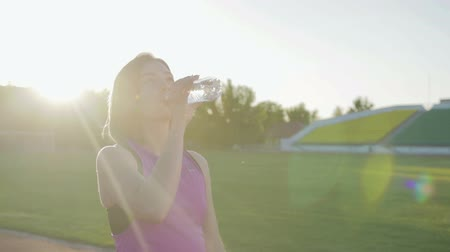 бегун трусцой : Beautiful fitness girl drinking water from a bottle during a workout. Steadicam shot Стоковые видеозаписи