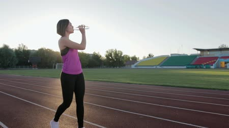 koňský ohon : Beautiful fitness girl drinking water from a bottle during a workout. Steadicam shot Dostupné videozáznamy