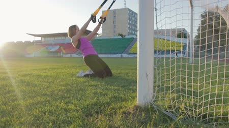 cross training : Beautiful fitness girl trains at the stadium. A young athlete is engaged with loops on the field in the football goal. Steadicam shot