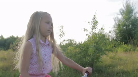 peyzajlı : A beautiful, little girl with long blond hair in a pink skirt rides a kids bicycle across the field, she is happy and smiling. Wind in her hair. Summer sunny weather