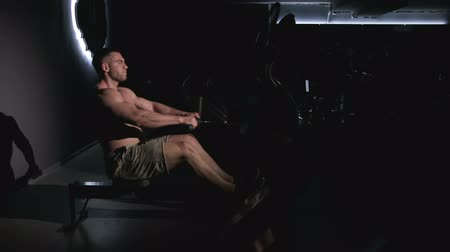 quadriceps : Midhty, handsome, a bodybuilder, an athlete trains the muscles of the back, triceps and quadriceps in the gym