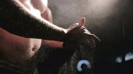 vigorous : Bodybuilder puts on the palm of magnesia, close-up, backlit