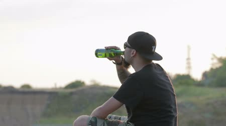 exemption : A carefree, young, friendly dude sits on a rock above the sea and drinks beer. Hes wearing a black t-shirt and shorts and a black baseball cap. Stock Footage