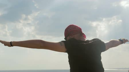 gust of wind : Carefree, young guy stands on a cliff above the sea and enjoys. He spread his hands, the wind blew on him. The guy is happy and amicable. He is dressed in a black t-shirt and shorts.
