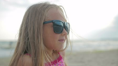brisa : Little beautiful daughter with long hair and a pink swimsuit sitting on the beach in sunglasses, on the background of the sea
