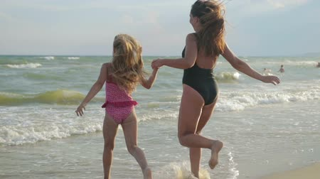 flee : Mom and daughter in swimsuits, hold hands and flee along the beach to swim in the sea. Blowing a breeze through hair, they are careless and happy. Slow motion