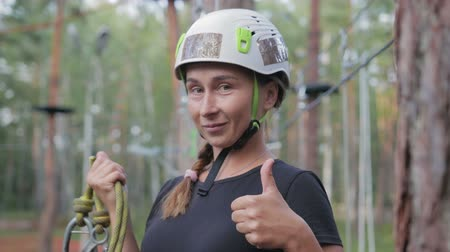 skypark : Young beautiful brunette overcomes obstacles in the rope town. A girl with a white helmet on her head and a rope in her hand shows like after passing the track Stock Footage