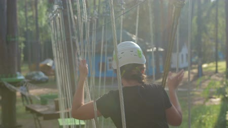 skypark : Young beautiful brunette overcomes obstacles in the rope town. A girl with a white helmet on her head and protective gear is on the track