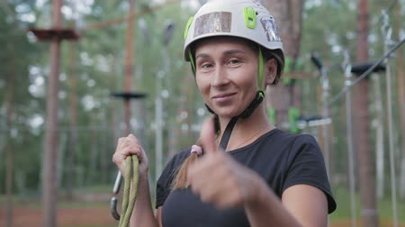 subir escalera : Young beautiful brunette overcomes obstacles in the rope town. A girl with a white helmet on her head and a rope in her hand shows like after passing the track Archivo de Video