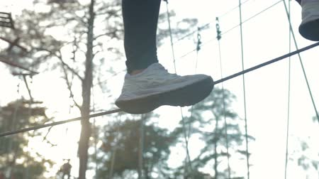 altura : Close-up of the girls feet goes and balances on the rope