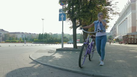 ciclista : Image of a beautiful, young girl with a pigtail, in a denim suit and sunglasses, who walks leisurely down the street with a glass of coffee and rolls a purple Bicycle.