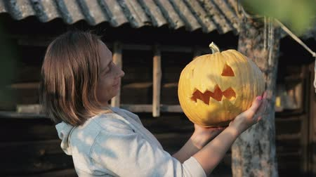 hag : The girl holds Jacks lantern in her hands and admires the pumpkin, and then turns and shows evil and terrible emotions. Happy Halloween Stock Footage