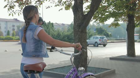álmodozó : Image of a beautiful, young girl with a pigtail, in a denim suit and sunglasses, who walks leisurely down the street with a glass of coffee and rolls a purple Bicycle.