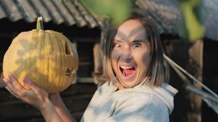 grão : The girl holds Jacks lantern in her hands and admires the pumpkin, and then turns and shows evil and terrible emotions. Happy Halloween Stock Footage