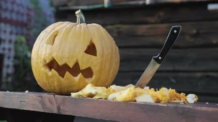 grão : Close-up of a pumpkin and a lantern Jack lying on the table, next to cutting vegetables. Next to the knife sticks with a black handle. 1080p Stock Footage