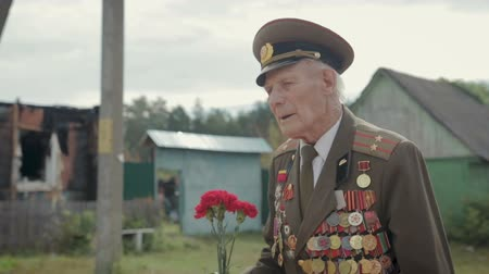 солдаты : An elderly gray-haired veteran of the great Patriotic war and world war II in uniform with many badges and orders goes through the village. Grandpa is in the hands of red carnations. Steadicam shot Стоковые видеозаписи
