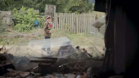 komutan : Veteran of the great Patriotic war and world war II in uniform with many badges and orders passes by an old wooden house destroyed by fire. 1080p