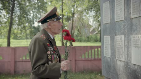 komutan : An elderly gray-haired veteran of the great Patriotic war and world war II in uniform with many badges and orders stands near the monument. My grandfather is in the hands of red carnations. Steadicam shot