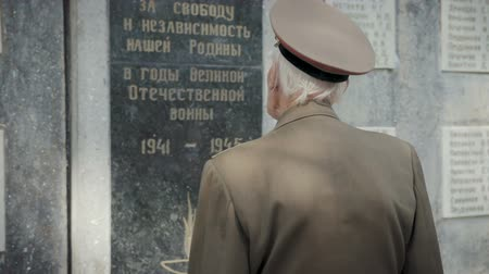 командир : An elderly gray-haired veteran of the great Patriotic war and world war II in uniform with many badges and orders stands near the mass grave. The grandfather remembers horrors of military operations, destruction and death of people. Steadicam shot