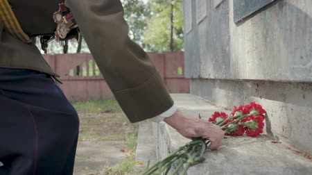 komutan : An elderly gray-haired veteran of the great Patriotic war and world war II in uniform with many badges and orders puts red flowers to the monument. Steadicam shot