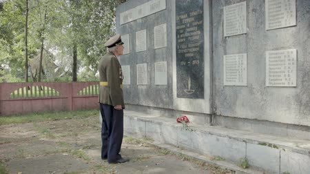 komutan : An elderly gray-haired veteran of the great Patriotic war and world war II in uniform with many badges and orders stands near the mass grave. The grandfather remembers horrors of military operations, destruction and death of people. Steadicam shot