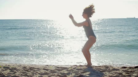 plage : Beautiful, sporty girl in a black swimsuit and sunglasses doing exercises in the morning on the beach