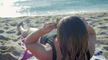 plage : Beautiful, sporty girl with wet hair, in a black swimsuit lying on the beach, ocean and wearing sunglasses. 1080p