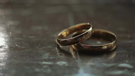 fiancee : Two wedding rings lie on a wooden surface. Close up