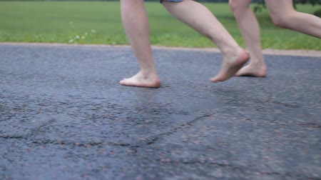 pace : Romantic date. Two people, a woman and a man walk the road cheerfully. People walk barefoot on wet asphalt. Steadicam shot