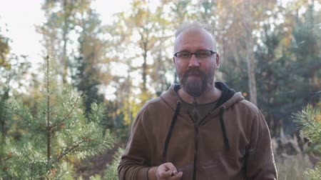 garibaldi : Portrait of a bald guy with glasses and a pigtail, with a beard Garibaldi, who smokes a cigarette. He is wearing a sweatshirt and stands in the autumn forest