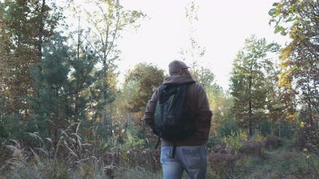 wandering : The guy slowly walks in the autumn forest and enjoys nature, wearing a jacket and jeans on his back hanging backpack. Hiking in the forest, taiga