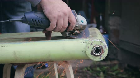 angle grinder : The person makes cleaning of an old heating radiator by an angular grinding machine, sparks fly out from under a circle. Man works with bare hands without protective gloves, risk of injury Stock Footage