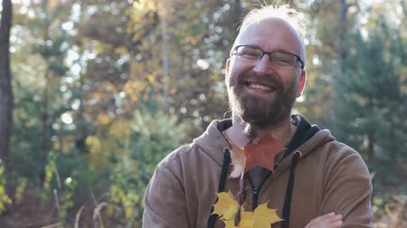 garibaldi : Portrait of a happy, bearded dude with glasses and a pigtail on his chin, in which maple leaves are woven. He smiles with crooked teeth