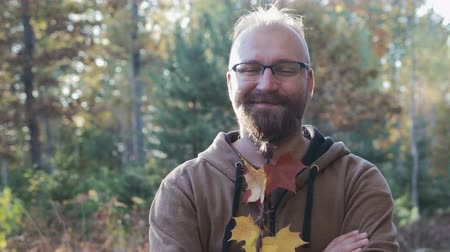 haver : Portrait of a happy, bearded dude with glasses and a pigtail on his chin, in which maple leaves are woven
