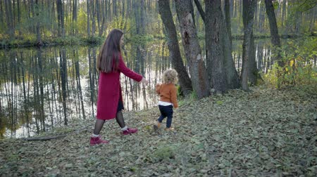 pletený : A young mother with a young son walking in the autumn Park among the fallen leaves near the lake. Autumn concept. Stylish mom and son on a lake background