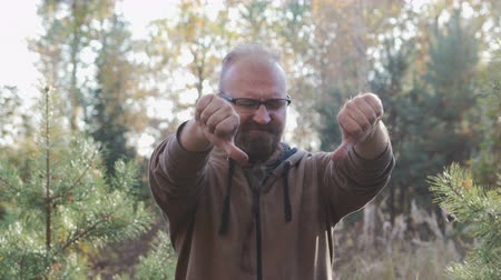 disapprove : Portrait of a young, adult man with glasses and beard who shows a bad sign of frustration with both hands, thumb down. He nods in different directions and frowns. The concept of failure Stock Footage