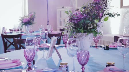 artigos de vidro : Luxury, purple table setting dishes and flowers for banquets and celebrations. Steadicam shot Vídeos