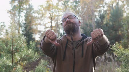 disapprove : Cute, young man with glasses and a beard showing bad gesture of dissent, with the thumb down Stock Footage