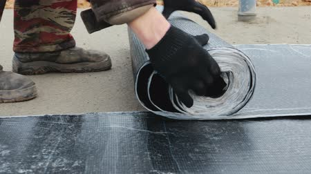 kanalizace : Extremely close-up of the hand of the worker performing unwinding of a roll of waterproofing material on a fresh concrete floor screed in the house