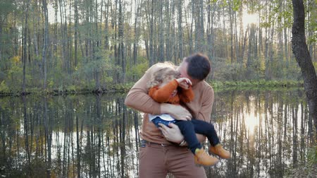 poblíž : A handsome father holds a small, curly-haired son in his arms near the lake in the Park, they have fun, play and fool around. In the lake reflections trees. The concept of happiness
