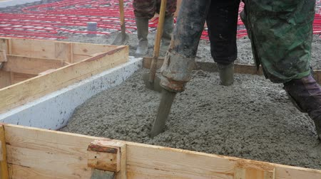 postřikovač : Steadicam shot of builders performing the pouring of the concrete screed floor heating on the ground from the spray machine