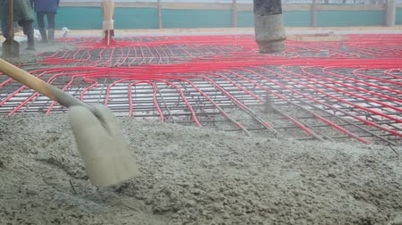 kaloryfer : Steadicam shot of builders performing the pouring of the concrete screed floor heating on the ground from the spray machine