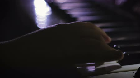 senfoni : Close-up of baby girls hands playing piano in a dark room Stok Video