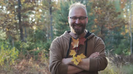 haver : Portrait of a bald guy with glasses and a beard, which are woven maple leaves.The guy smiles and rejoices