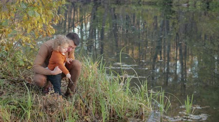 отцовство : Happy, young father spends time on the shore of a forest lake with a beautiful, small, blond son. The water reflects the trees. The boy hits the water with a stick. Concept of family Стоковые видеозаписи