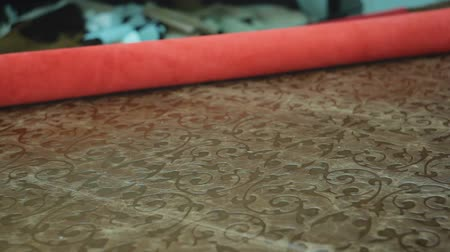 süet : Close-up of a roll of natural red leather, spread on the table for further processing and production of things in the workshop